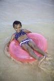 Kleines Mädchen, das auf ein rosa Floss schwimmt Stockfotos