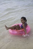 Kleines Mädchen, das auf ein rosa Floss schwimmt Stockbild