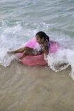 Kleines Mädchen, das auf ein rosa Floss schwimmt Stockfotografie