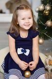 Kleines Mädchen, das auf ein Wunder in den Weihnachtsdekorationen wartet lizenzfreies stockfoto