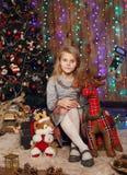 Kleines Mädchen, das auf ein Wunder in den Weihnachtsdekorationen wartet lizenzfreie stockfotografie