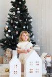 Kleines Mädchen, das auf ein Wunder in den Weihnachtsdekorationen wartet stockbilder