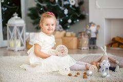 Kleines Mädchen, das auf ein Wunder in den Weihnachtsdekorationen wartet lizenzfreie stockfotos