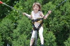 Kleines Mädchen, das auf eine Trampoline springt stockfotografie