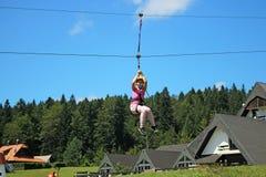 Kleines Mädchen, das auf eine Ziplinie schiebt Stockfotos