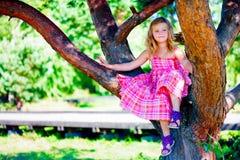 Kleines Mädchen, das auf einem Baum sitzt Lizenzfreie Stockfotos