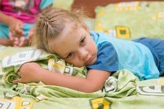 Kleines Mädchen, das auf einem Doppelbett und erschrockenen Blicken in Abstand sitzt Stockfoto
