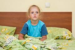 Kleines Mädchen, das auf einem Doppelbett und erschrockenen Blicken in Abstand sitzt Stockbilder