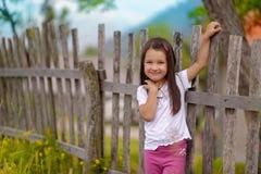 Kleines Mädchen, das auf einem Hintergrund eines alten Zauns steht Stockfotografie