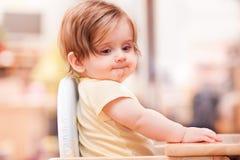 Kleines Mädchen, das auf einem Holzstuhl sitzt stockfotos