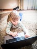 Kleines Mädchen, das auf einem Notizbuch spielt Lizenzfreie Stockbilder
