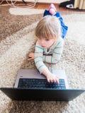 Kleines Mädchen, das auf einem Notizbuch spielt Lizenzfreie Stockfotografie