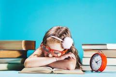 Kleines Mädchen, das auf einem offenen Buch in den lustigen roten Gläsern schläft stockbild