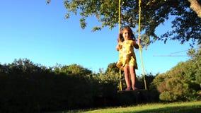 Kleines Mädchen, das auf einem Schwingen schwingt stock video