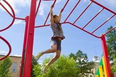Kleines Mädchen, das auf einem Spielplatz, hängender Weg entlang den Kletterstangen spielt Stockbild