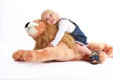Kleines Mädchen, das auf einem Spielzeuglöwe sich lehnt Lizenzfreies Stockbild