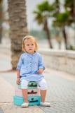 Kleines Mädchen, das auf einem Stapel Koffern sitzt Stockbild