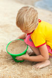 Kleines Mädchen, das auf einem Strand spielt Stockfotos