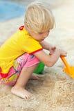 Kleines Mädchen, das auf einem Strand spielt Stockfotografie