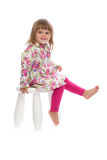 Kleines Mädchen, das auf einem Stuhl im Studio sitzt Stockbilder