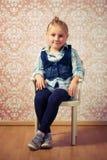 Kleines Mädchen, das auf einem Stuhl sitzt Lizenzfreies Stockbild