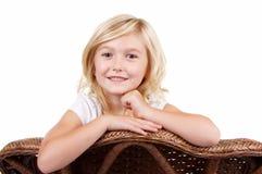 Kleines Mädchen, das auf einem Stuhl sitzt lizenzfreie stockbilder
