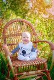 Kleines Mädchen, das auf einem Stuhl sitzt Stockfotos