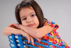 Kleines Mädchen, das auf einem Stuhl stillsteht Stockbild
