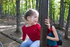 Kleines Mädchen, das auf einem Zaun im Wald schreit zur Mutter sitzt Lizenzfreie Stockfotografie