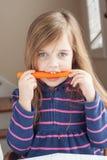 Kleines Mädchen, das auf einer Karotte beißt Stockfoto