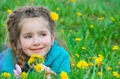 Kleines Mädchen, das auf Feld des Löwenzahns liegt Lizenzfreie Stockbilder