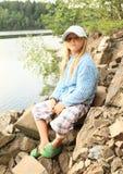 Kleines Mädchen, das auf Felsen sitzt Lizenzfreie Stockfotografie