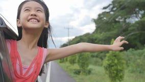 Kleines Mädchen, das auf Fenster-Auto, Familie reist auf Landschaft spielt stock video