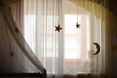 Kleines Mädchen, das auf Fensterbrett sitzt Lizenzfreies Stockfoto