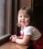Kleines Mädchen, das auf Fensterrahmen sich lehnt Lizenzfreie Stockfotos