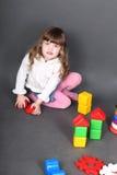Kleines Mädchen, das auf Fußboden sitzt Stockfotografie
