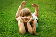 Kleines Mädchen, das auf Gras liegt Lizenzfreie Stockbilder