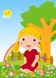 Kleines Mädchen, das auf Gras sitzt Stockbild