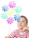 Kleines Mädchen, das auf großer Spielzeugwindmühle durchbrennt Stockbild
