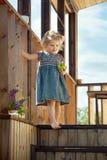Kleines Mädchen, das auf hölzerner Treppe eines Landhauses steht Stockfotos