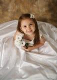 Kleines Mädchen, das auf Hochzeitskleid der Mammas versucht Stockfotos