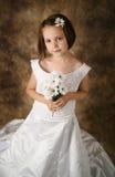 Kleines Mädchen, das auf Hochzeitskleid der Mammas versucht Stockfoto