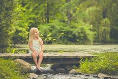 Kleines Mädchen, das auf Holzbrücke im Sommer stillsteht Stockfotos
