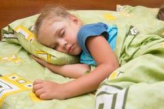 Kleines Mädchen, das auf ihrer Seite im Bett mit seiner Hand unter Kissen und mit einer Decke umfasst schläft Lizenzfreies Stockbild