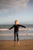 Kleines Mädchen, das auf Küste am Sonnenuntergang springt Stockfotos