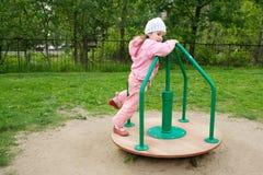 Kleines Mädchen, das auf Karussell spielt Lizenzfreies Stockbild