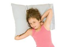 Kleines Mädchen, das auf Kissen aufwacht lizenzfreie stockfotos