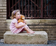 Kleines Mädchen, das auf konkretem Schritt mit Teddy Bear träumt Lizenzfreie Stockfotografie