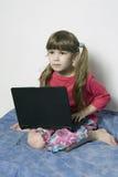 kleines Mädchen, das auf Laptop spielt Lizenzfreie Stockbilder