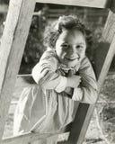 Kleines Mädchen, das auf Leiter sich lehnt Lizenzfreies Stockfoto